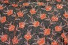 Photographed on black background. Orange and silver beads and sequins in floral pattern on mesh.