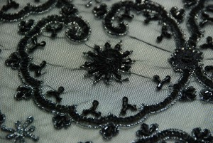 Sequinned black tulle in scallop design.