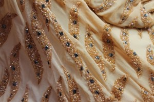 Pale orange chiffon with round pearl beads, iridescent bugle beads, and metallic geometric beads in a wave pattern