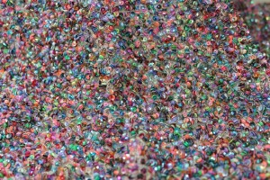 Multi-coloured scattered micro-sequins and beads on a pale nude mesh