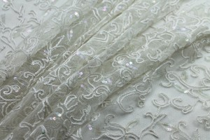 Ivory tulle embroidered with a swirl/leaf design, plus clear iridescent round sequins
