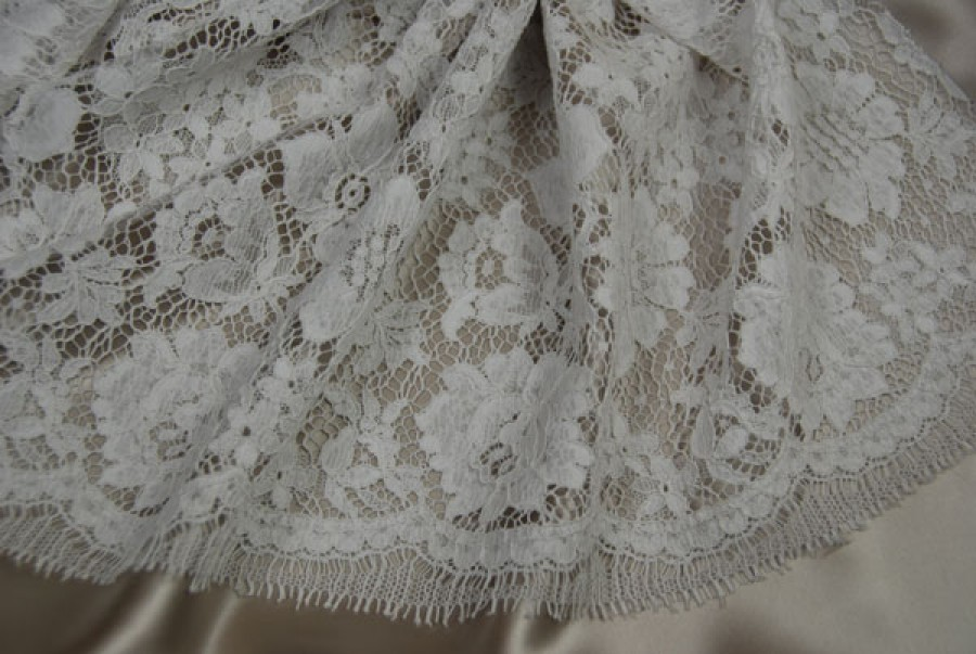 White corded lace with floral/rose cluster design. Double scallop