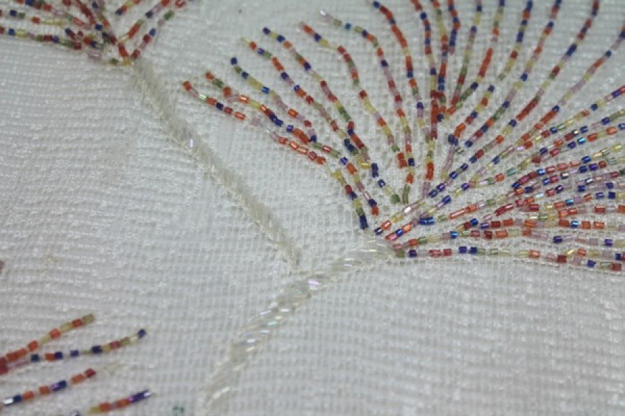 White lace mesh with multi-coloured bugle beads in a starburst pattern